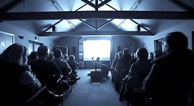 A picture of people watching a film in a rural community centre