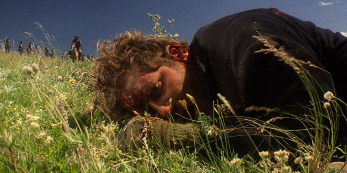 Man with a bloodied face lying in grass