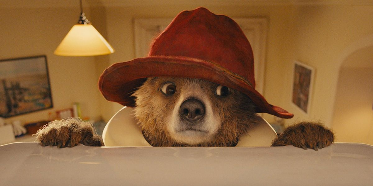 Paddington Bear hangs off the edge of a toilet