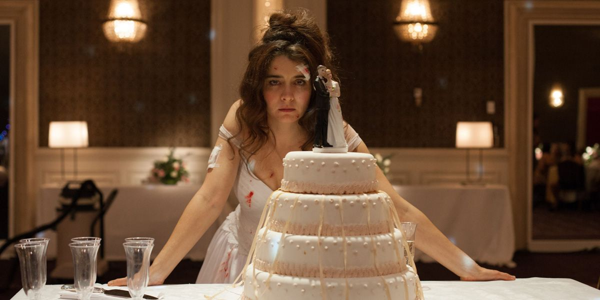 An angry Bride stares over her wedding cake