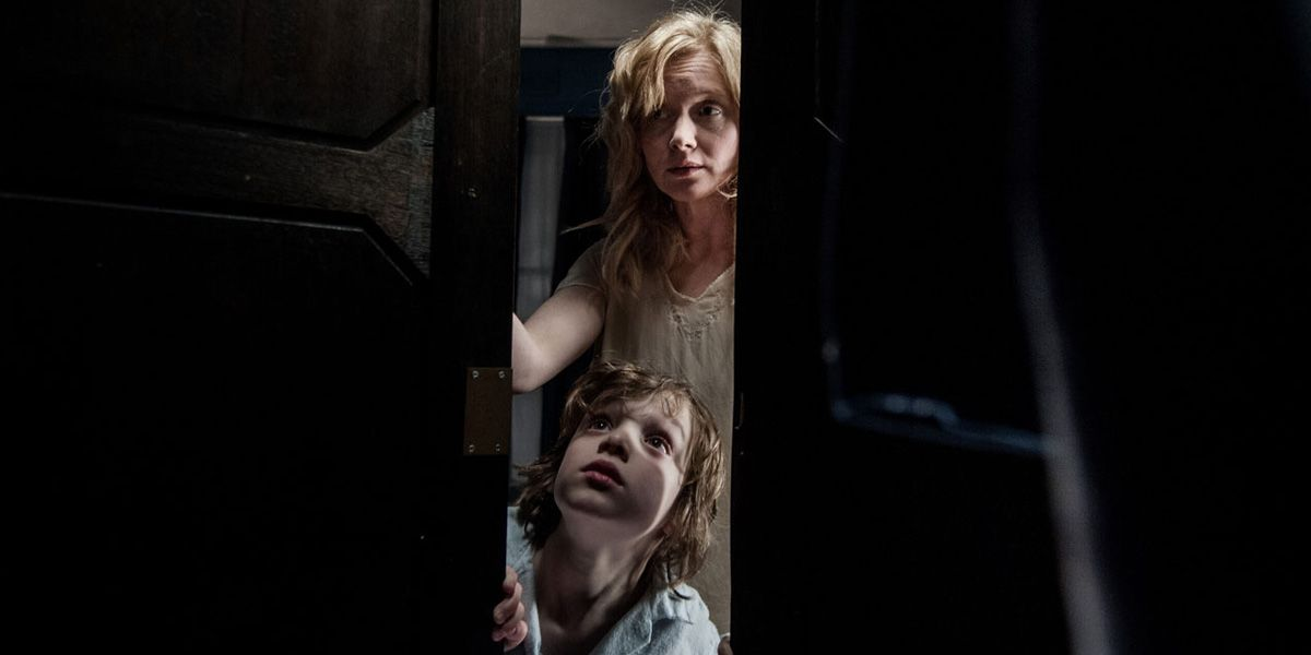 a mother and son peer into a dark closet