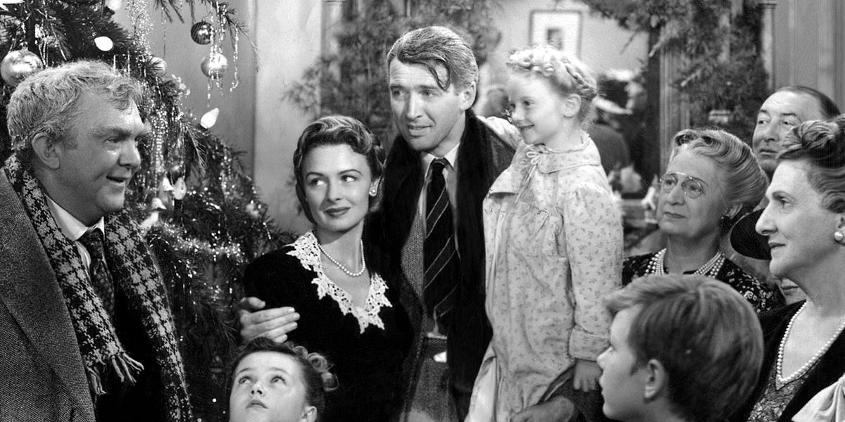 George Bailey stands round the Christmas tree with his family