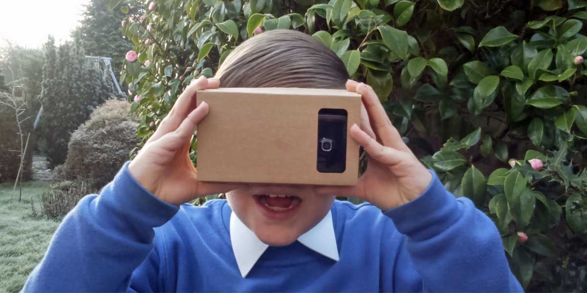 A boy holds up a google cardboard headset