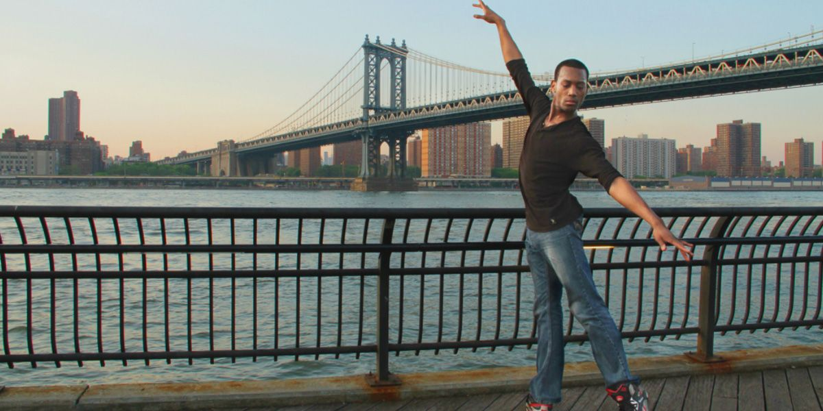 Frederick Davis strikes a ballet pose in front a bridge