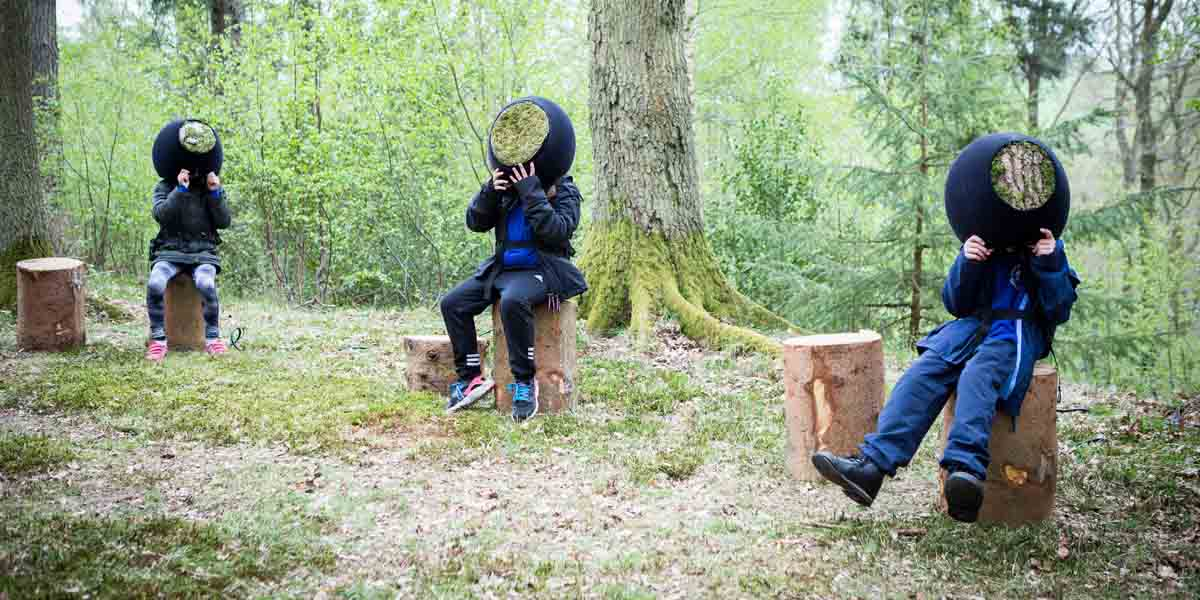 People wearing VR headsets sit in a forrest