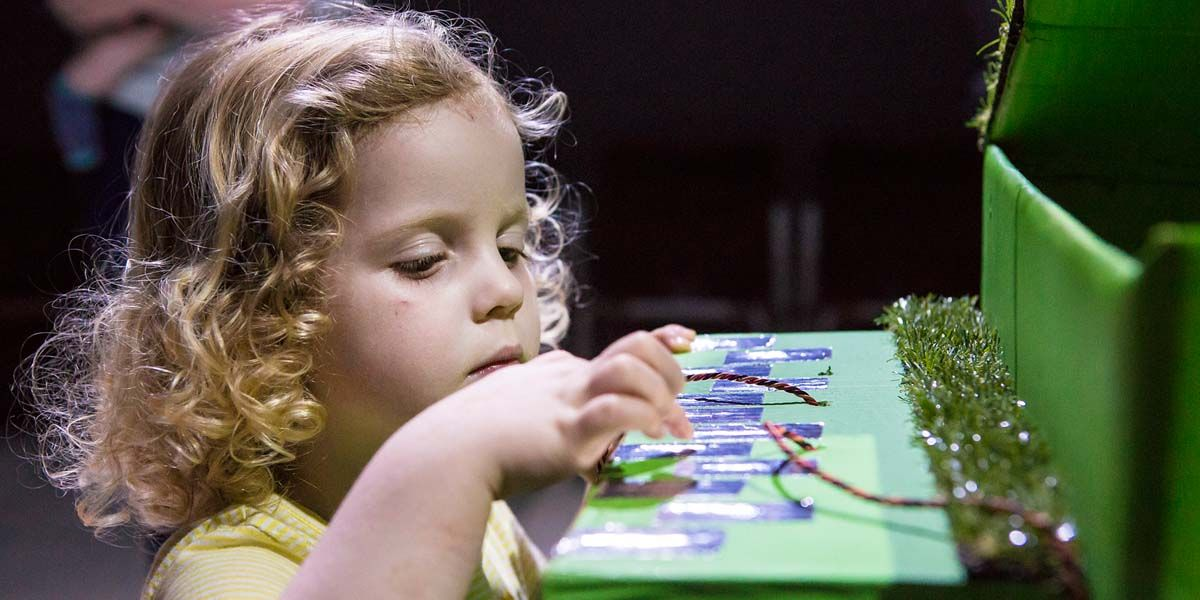 A girl plays a cardboard piano at the digital playground