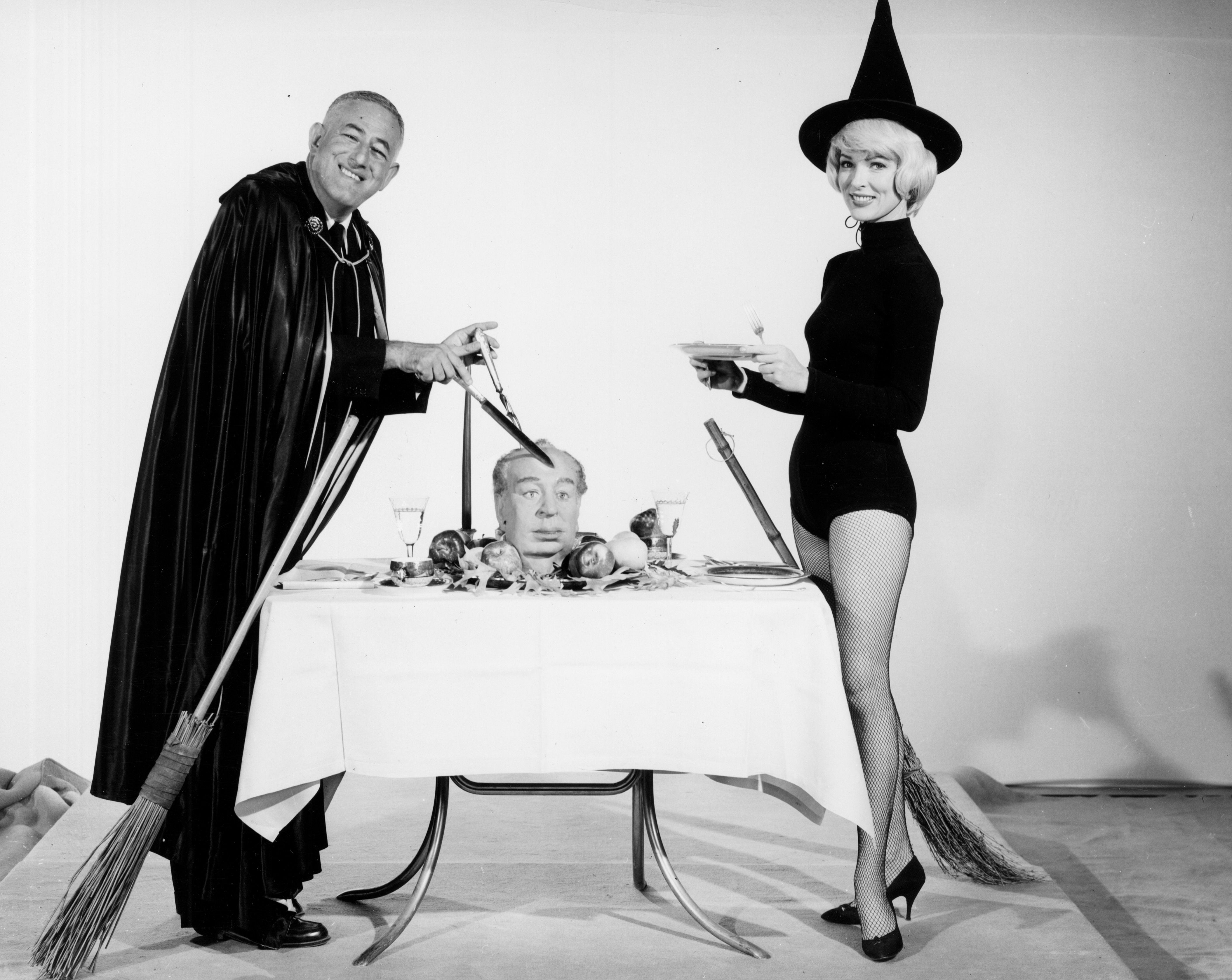 Promotional photo of film director William Castle accompanied by a witch.