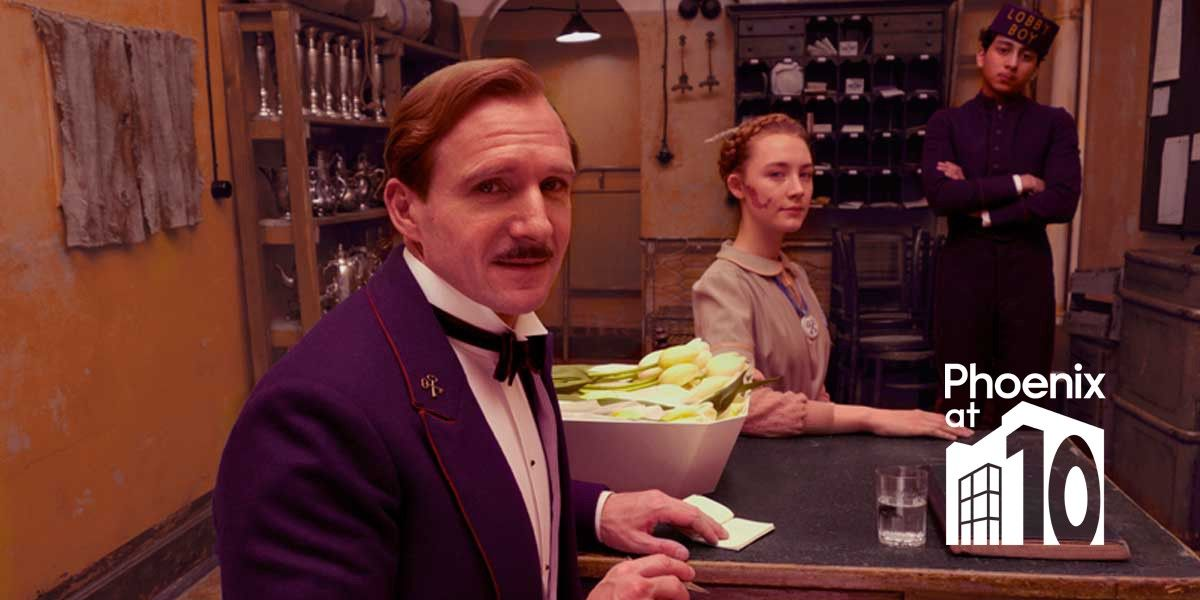 Ralph Fiennes in The Grand Budapest Hotel, seated in his purple uniform