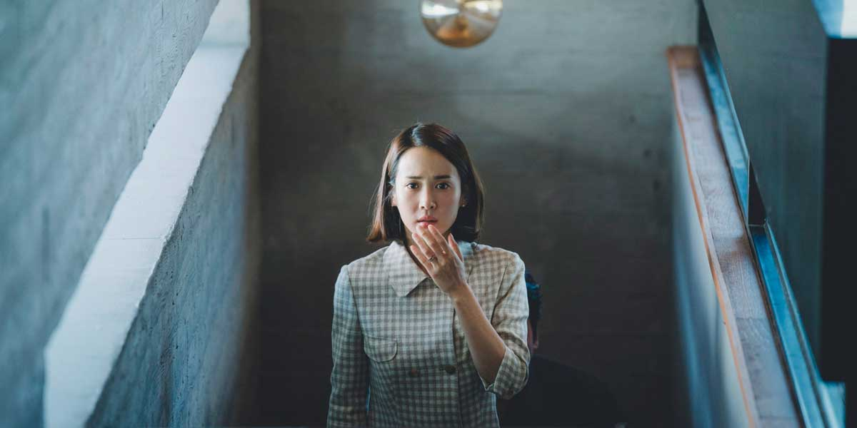 still from Korean film Parasite, woman walking up stairs with hand over mouth