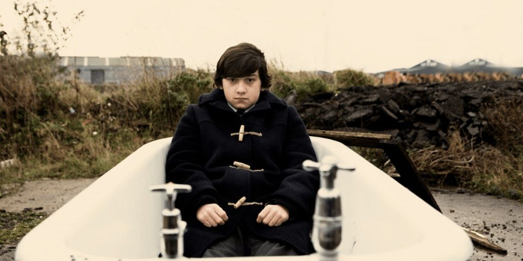 A wide shot of a teenage boy, clothed in an empty bathtub. From the film Submarine.