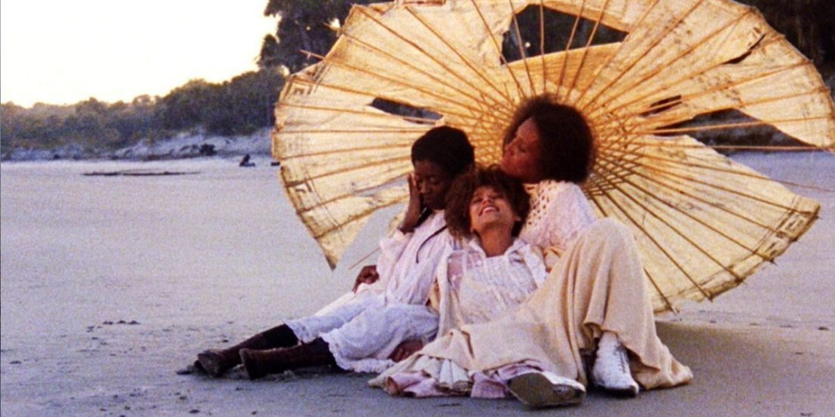An image of 3 women sitting on a beach under a large but ragged umbrella