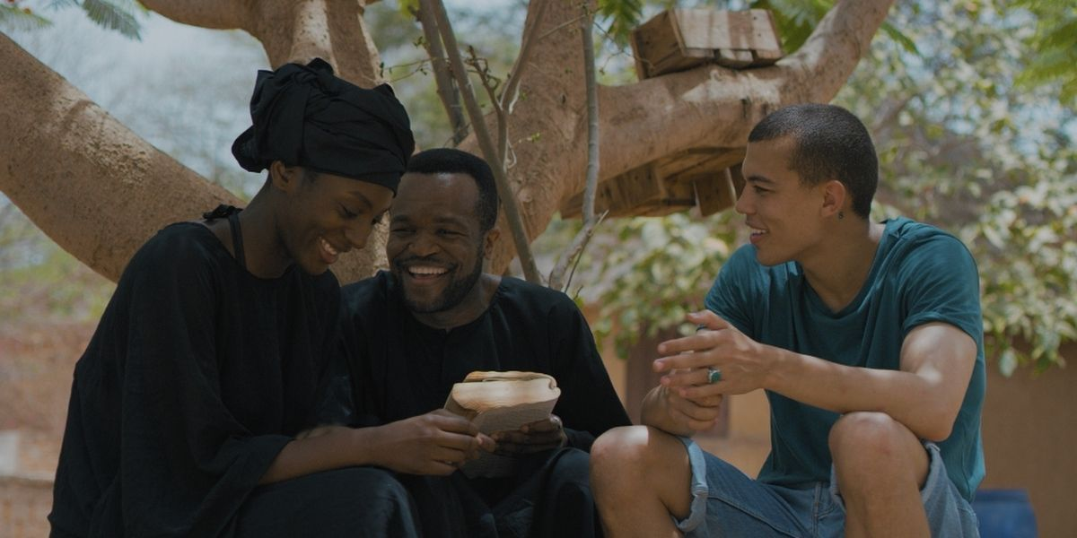 An image from the film White Colour Black, depicting three adults - one female, two male - laughing next to a tree