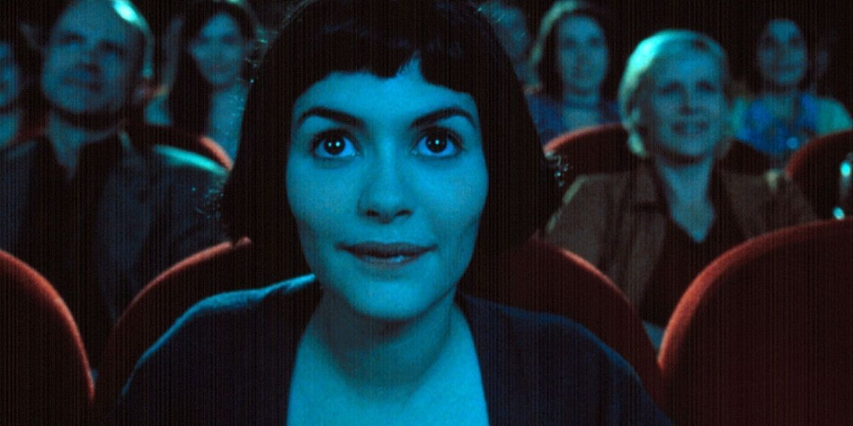 A young woman with short black hair is sat in a busy cinema screen, a still photo from Amelie