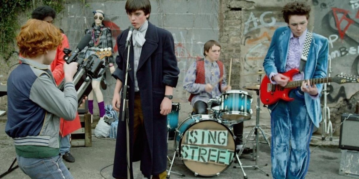 A teenage band are outside playing instruments with a young boy at the front videoing on an old-school video camera