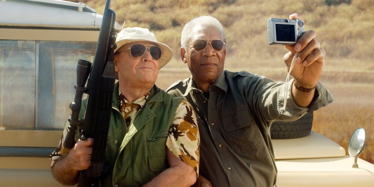 Jack Nicholson, who is holding a gun, and Morgan Freeman taking a selfie in front of a Jeep