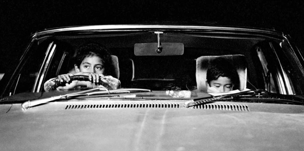 A medium shot of two young children in a car from the short film Two Cars, One Night