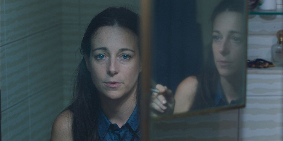 A medium shot of a woman's reflection in a mirror from the film A Common Crime