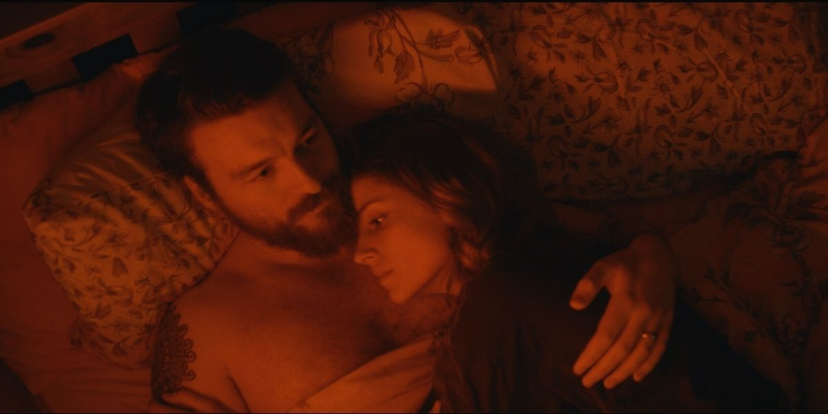 A medium shot of a man and woman laid in bed, from the thriller Rose: A Love Story