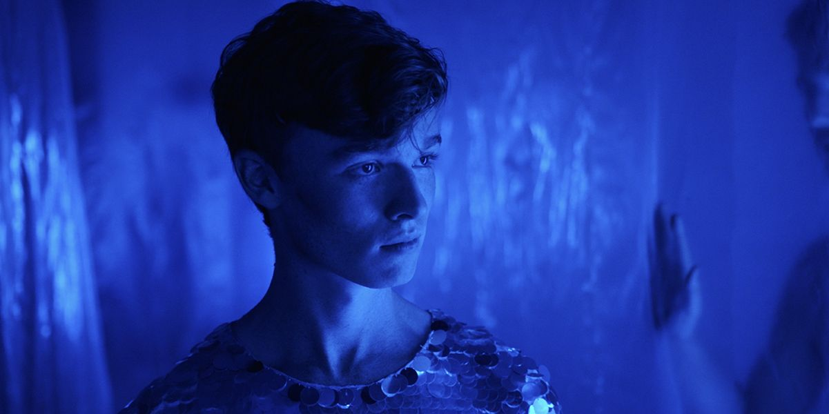 A medium shot of a young man bathed in a dark blue light from the film Sequin in a Blue Room