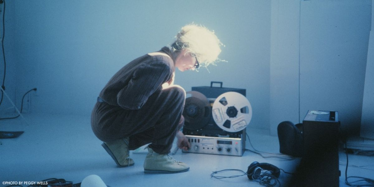 An establishing shot of a woman crouched in front of a recorder from the film Sisters with Transistors