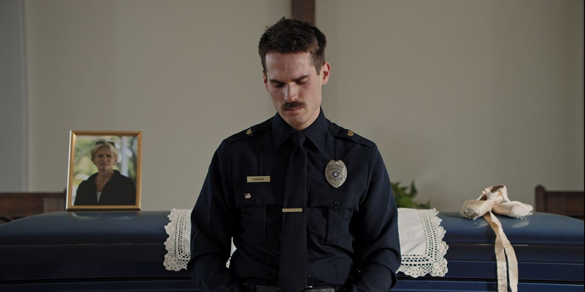 A medium shot of a police officer at a funeral from the film Thunder Road