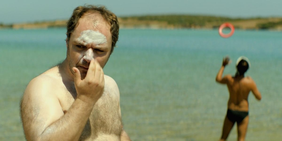 An image of a middle-aged man applying sun cream to his face while standing on the beach