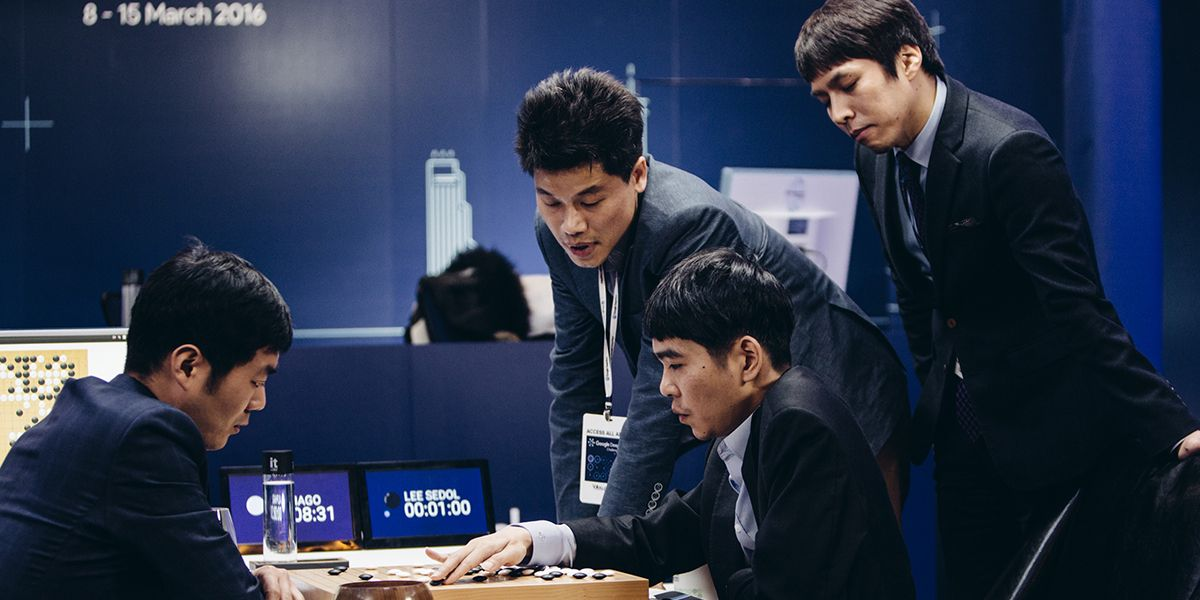 Image from the documentary AlphaGo, Lee Sendol contemplates his next move in the game of Go as a number of men watch on.