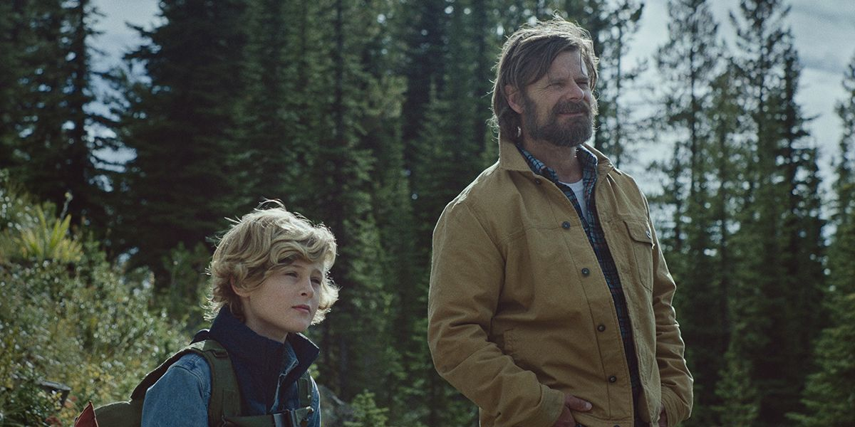 Image from the film Cowboys of father Troy and his trans son Joe, standing amongst a forest in Montana