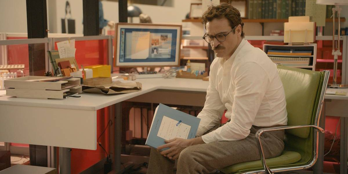 Image from the film Her, Theodore played by Joaquin Phoenix sits deep in thought at his desk in work.