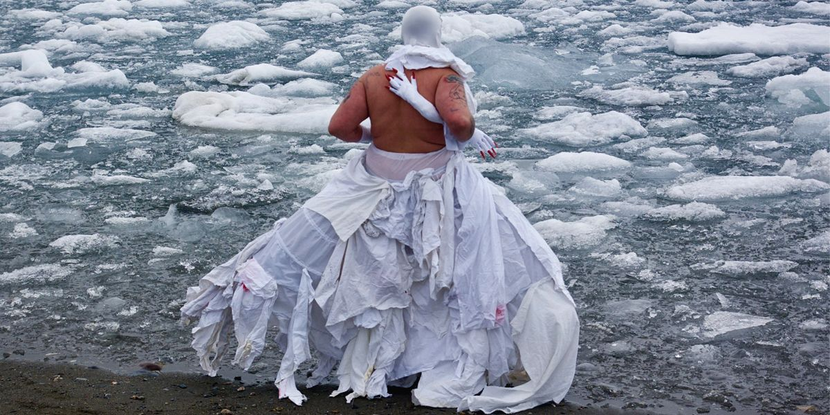 A photograph of a person on the sandy shore of an icy body of water. Bits of ice float on the surface of the water. The person is wearing a white costume which exposes their back. The bottom part of the costume is a wide skirt made from various rag-like layered sheets down to the ground. Across their back is a white arm-shaped object with a hand and red, pointy nails. Another of these can be seen coming out from under their right arm. Part of the costume wraps around the person's neck. Their head is covered with a tight white material.