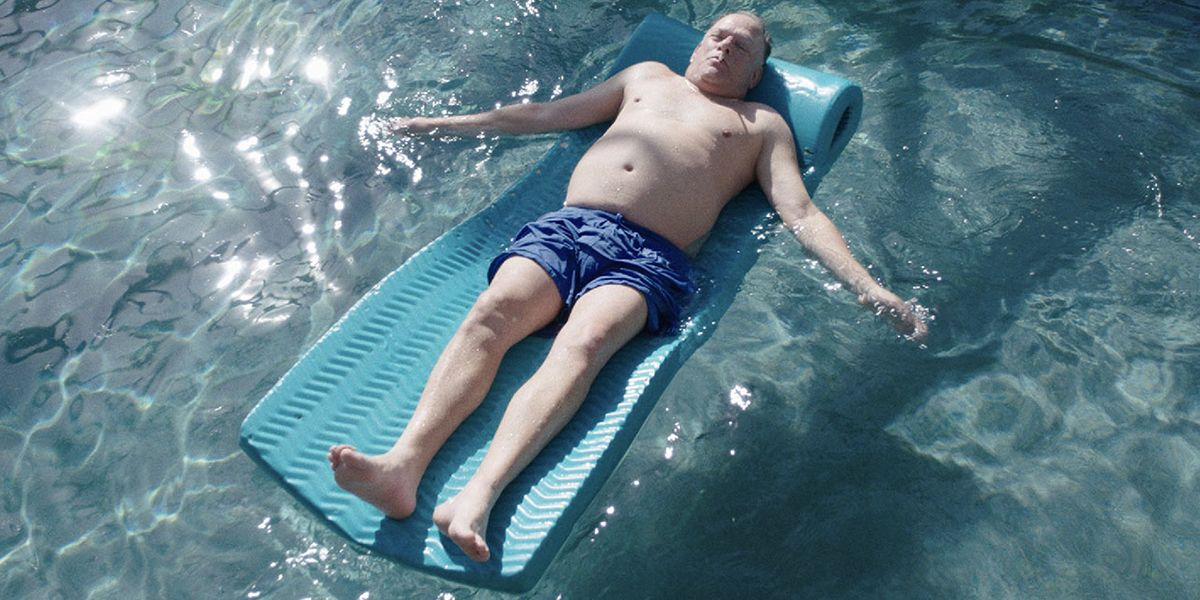 A close up of a man laid on a lilo floating in a swimming pool