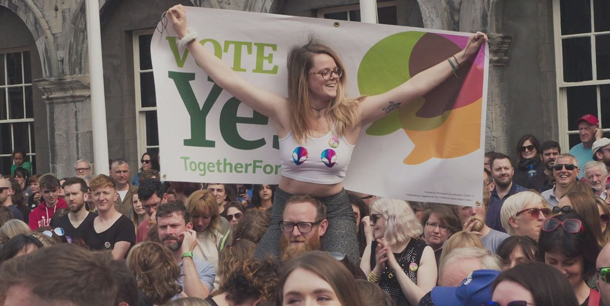 A young woman sits on a man's shoulders with a banner celebrating the result of the Irish referendum on abortion.