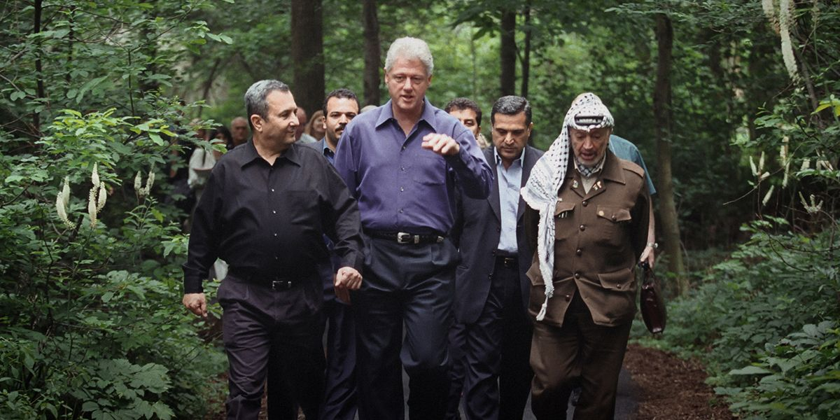 President Bill Clinton, flanked by Middle Eastern political leaders, walks through a wooded area.