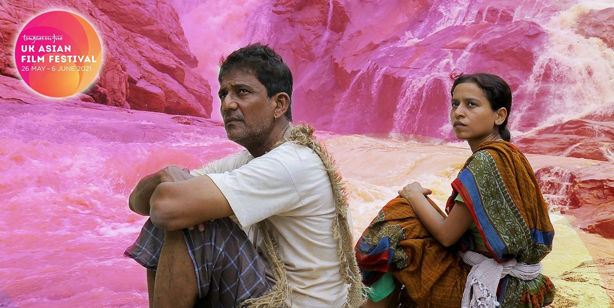 An Indian man and a young girl sit beside each other amidst a rocky landscape