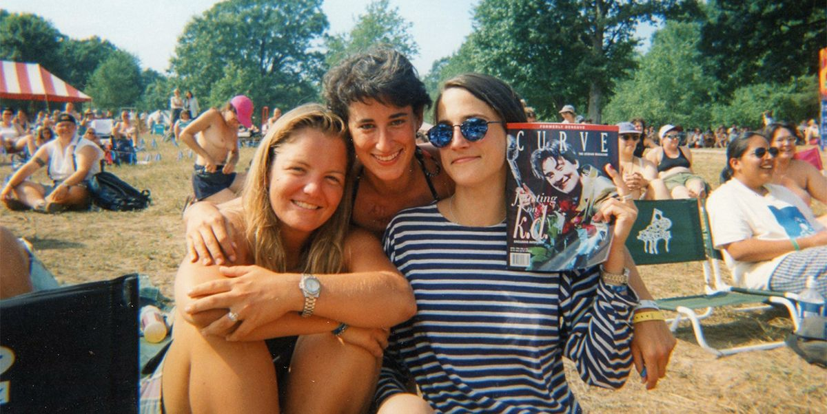 Three young women pose together for a photograph at a music festival, one holding a copy of Curve magazine.
