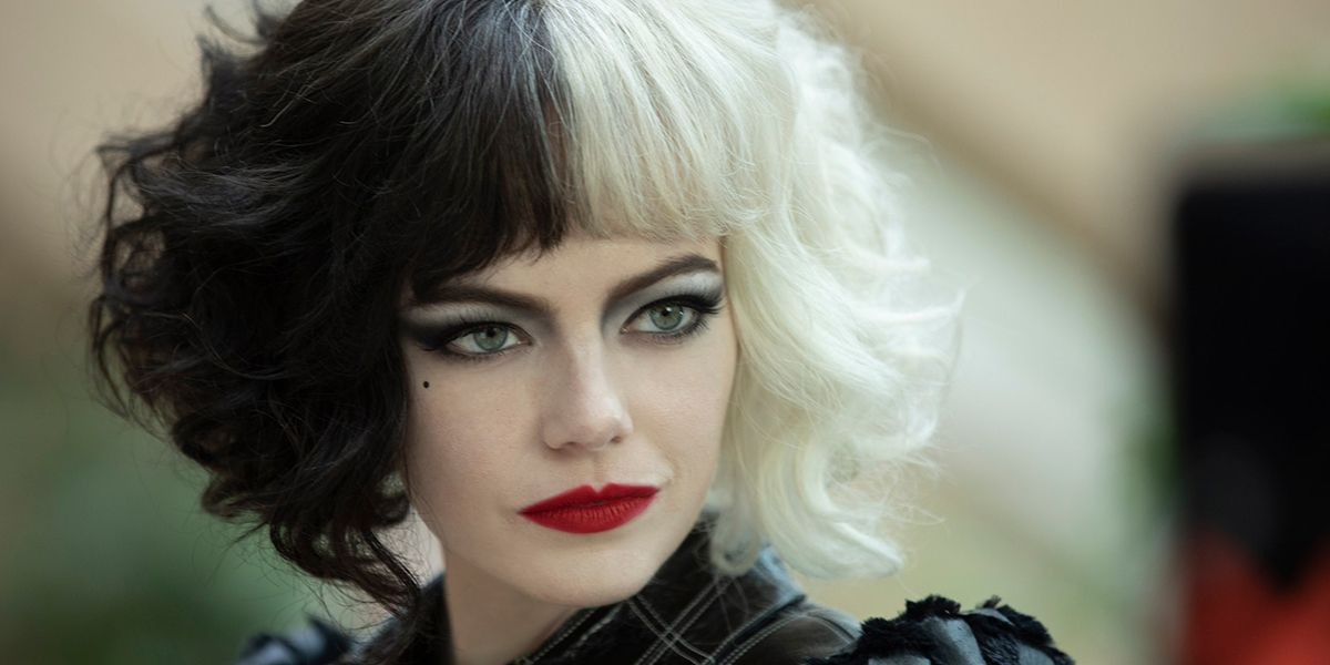 A young woman with distinctive black and white hair, this is Cruella de Vil played by Emma Stone.