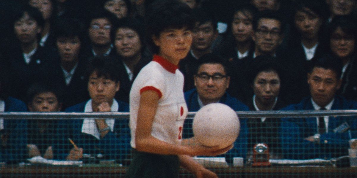 A member of the Japanese women's volleyball team prepares to serve as a packed audience watches on.