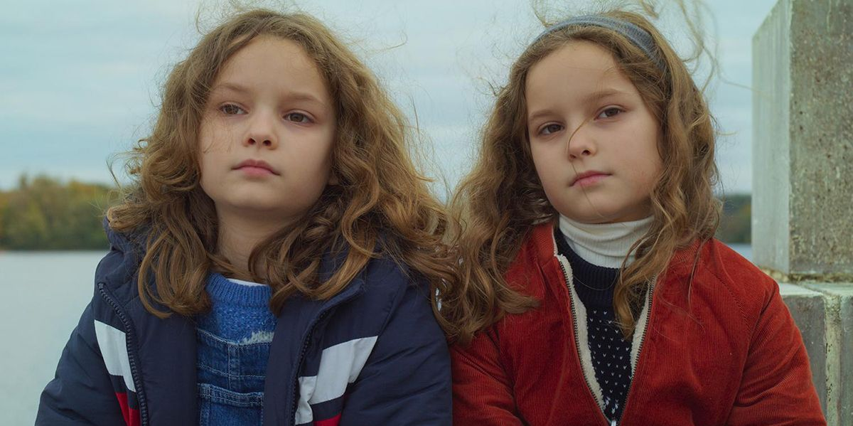 Two young curly haired twin girls stand shoulder to shoulder