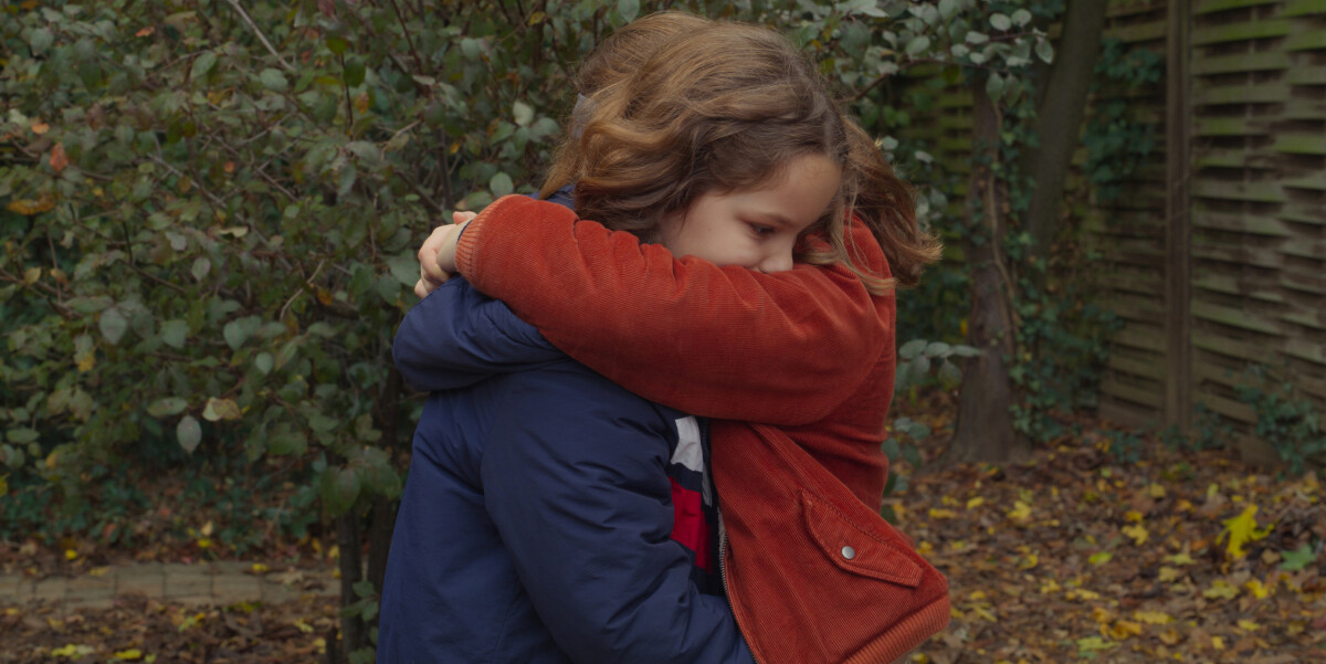 Two young girls embrace in front of an autumn scene