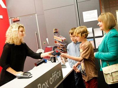 A picture of children receiving audio describe headphones at box office