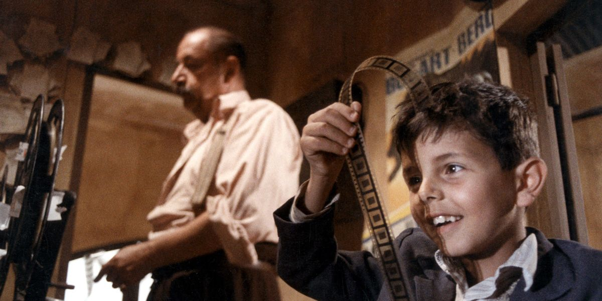 Toto' looks at a reel of film in Cinema Paradiso