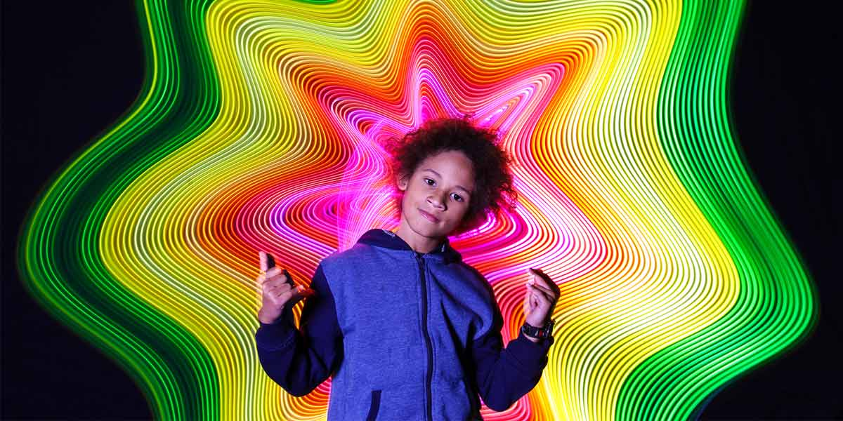 a child stands in front of a light painting