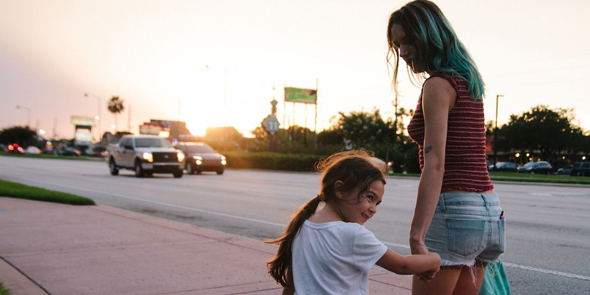 Mother and daughter hold hands in The Florida Project