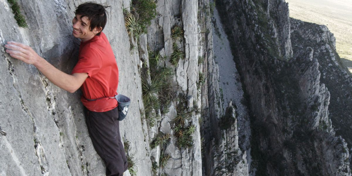 A climber hangs off the side of a cliff in Mountain