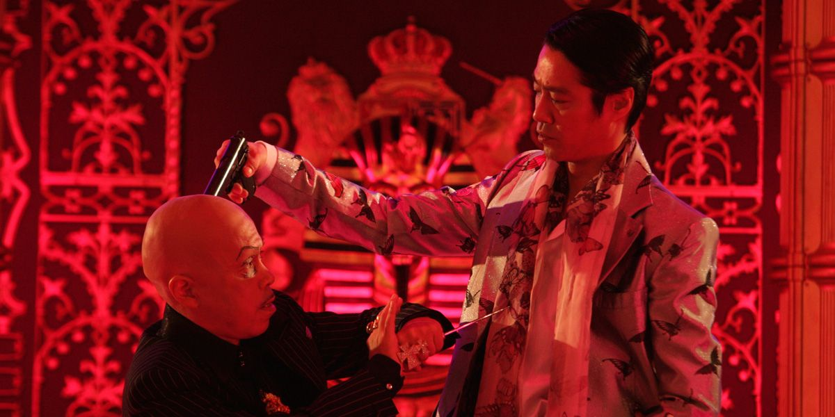 A gangster holds a gun to somebody's head in Takashi Miike's Mole Song