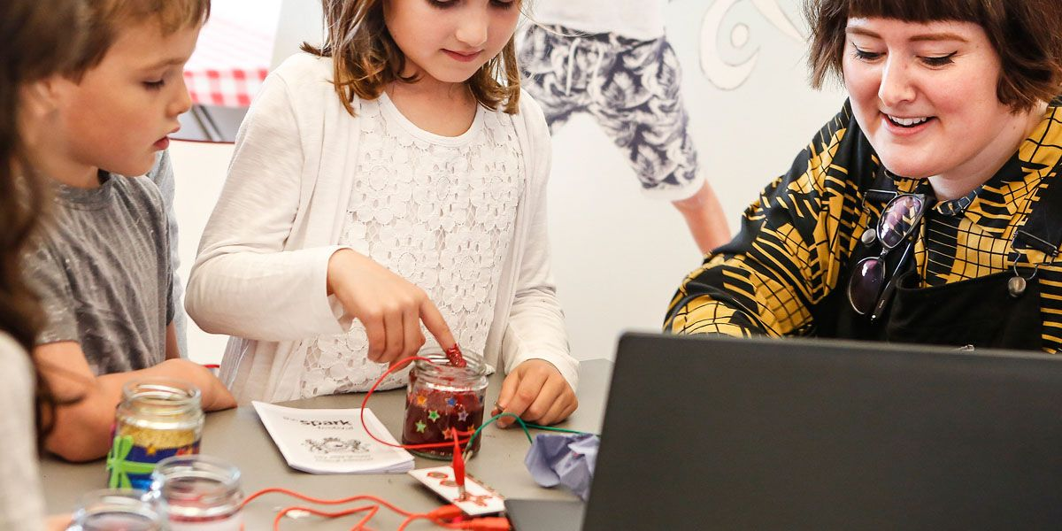 A child uses the makey makey at a family workshop